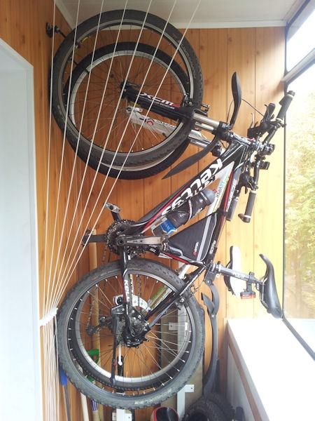 фото: хранение велосипеда на крюках на балконе