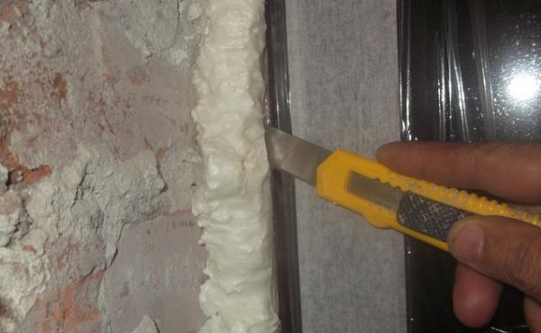 срезаем излишки пены с окна для откосов