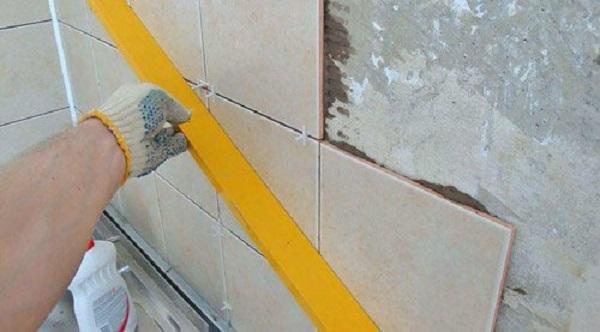 прикладываем строительный уровень к плитке