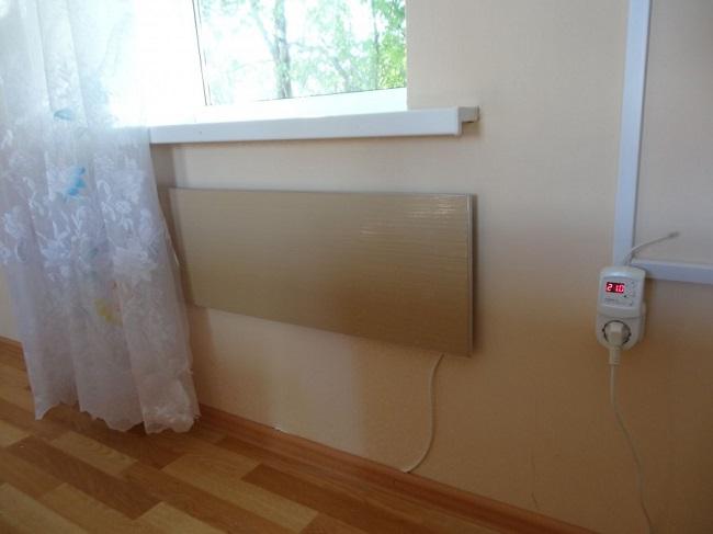 настенный керамический обогреватель под окном