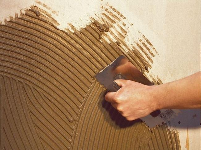 нанесение клея на стены гребенкой